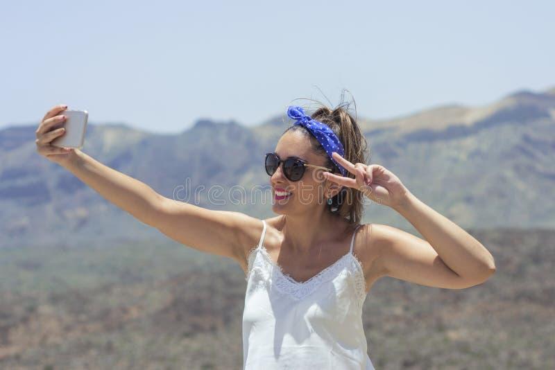 Mujer hermosa que toma un selfie encima de una montaña, con las hermosas vistas de los alrededores del teide detrás de ella, con imagen de archivo libre de regalías