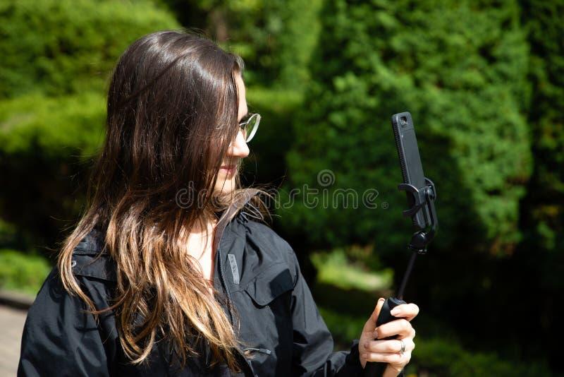 Mujer hermosa que toma una imagen con un teléfono y un palillo del selfie en una selva tropical fotografía de archivo