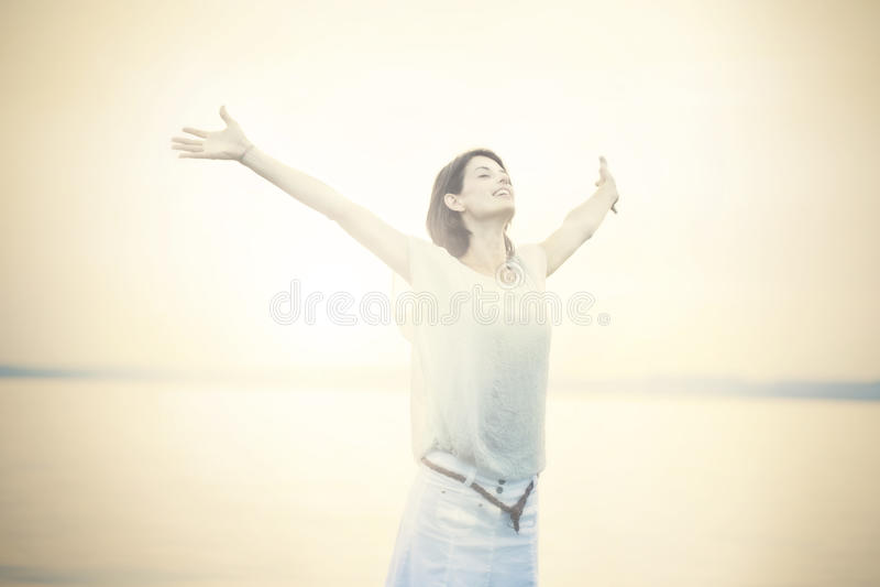 Mujer hermosa que toma una respiración profunda en la puesta del sol fotografía de archivo