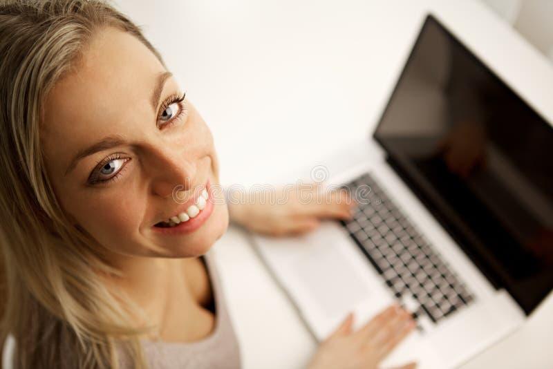 Mujer hermosa que trabaja en su computadora portátil fotos de archivo