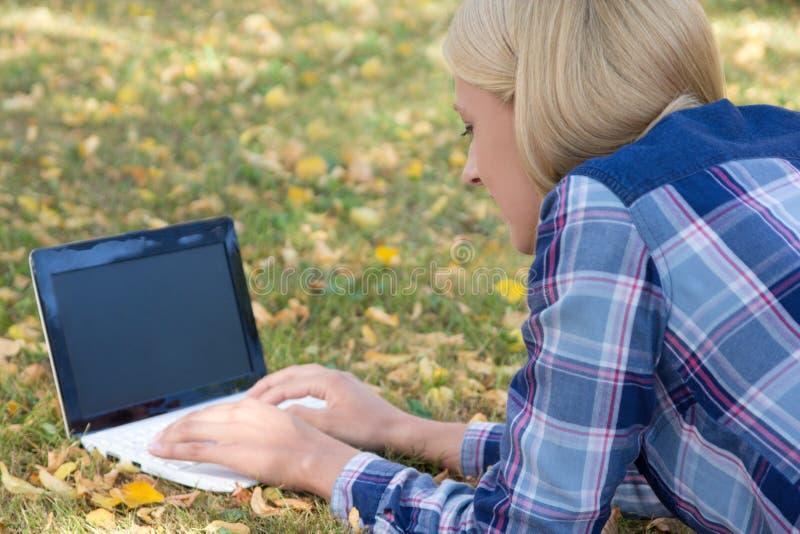 Mujer hermosa que usa el ordenador portátil con la pantalla vacía en parque del otoño imagen de archivo libre de regalías