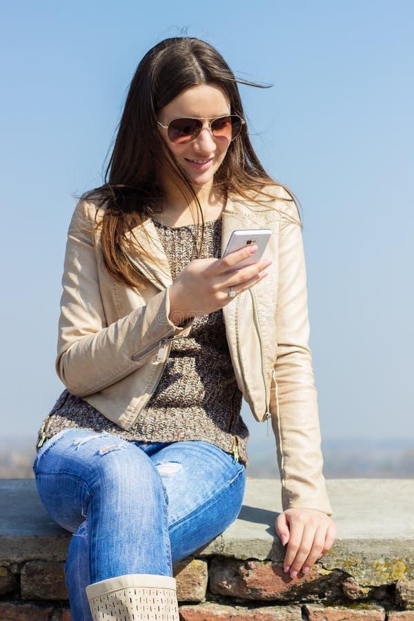 Mujer hermosa que usa smartphone imagenes de archivo