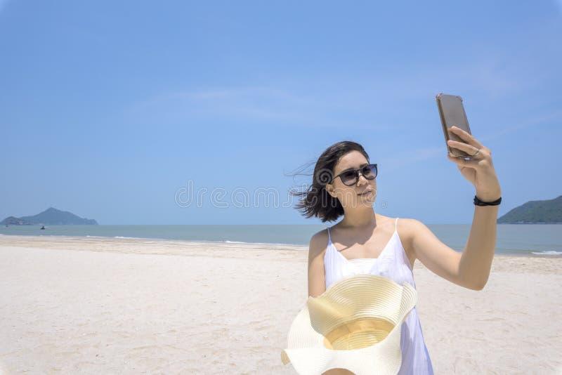 Mujer hermosa que usa smartphone en la playa imagen de archivo