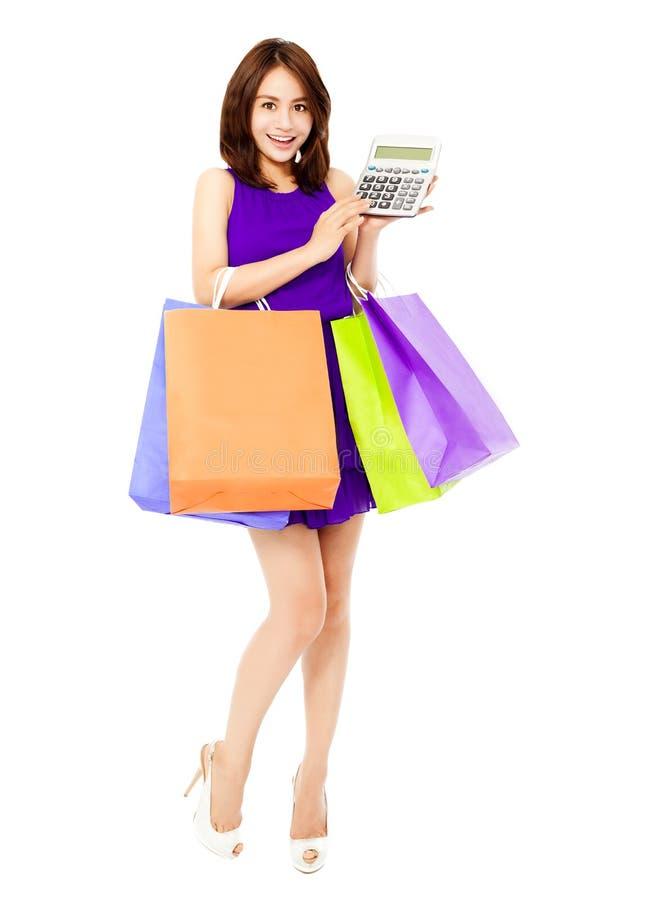 Mujer hermosa que usa una calculadora y sosteniendo bolsos imágenes de archivo libres de regalías