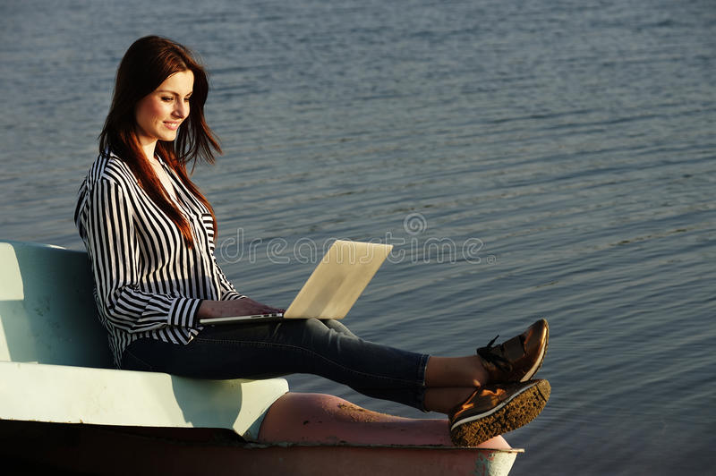 Mujer hermosa que usa una computadora portátil imágenes de archivo libres de regalías