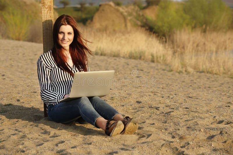 Mujer hermosa que usa una computadora portátil imagenes de archivo