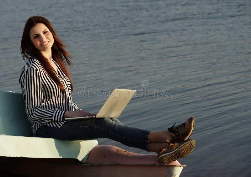 Mujer hermosa que usa una computadora portátil foto de archivo libre de regalías