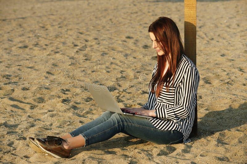 Mujer hermosa que usa una computadora portátil imagen de archivo libre de regalías