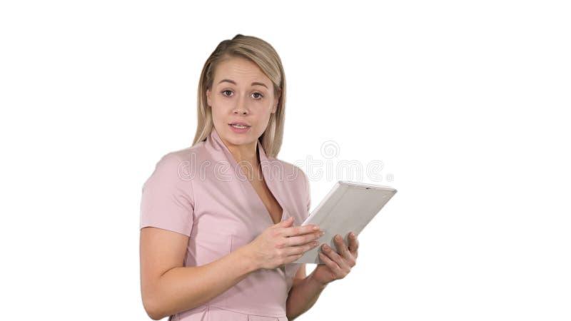 Mujer hermosa que usa una tableta digital y hablando con la cámara en el fondo blanco imagenes de archivo