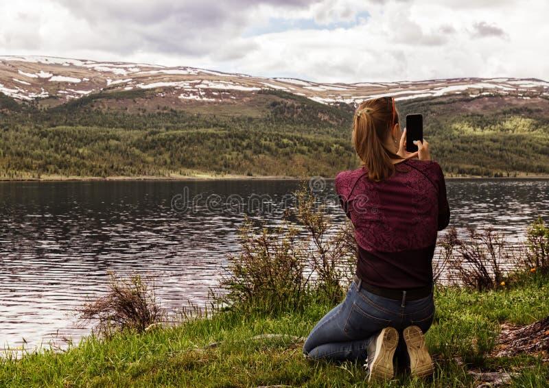 Mujer hermosa sola que se sienta en la orilla de un lago de la montaña y tomar una foto en un smartphone fotos de archivo