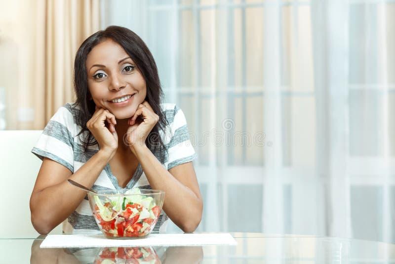 Mujer hermosa sonriente en cocina fotografía de archivo