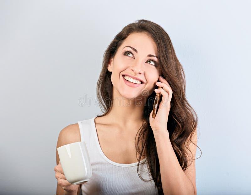 Mujer hermosa sonriente feliz que habla en el teléfono móvil y que sostiene la taza de café en fondo azul con el espacio vacío de fotografía de archivo libre de regalías