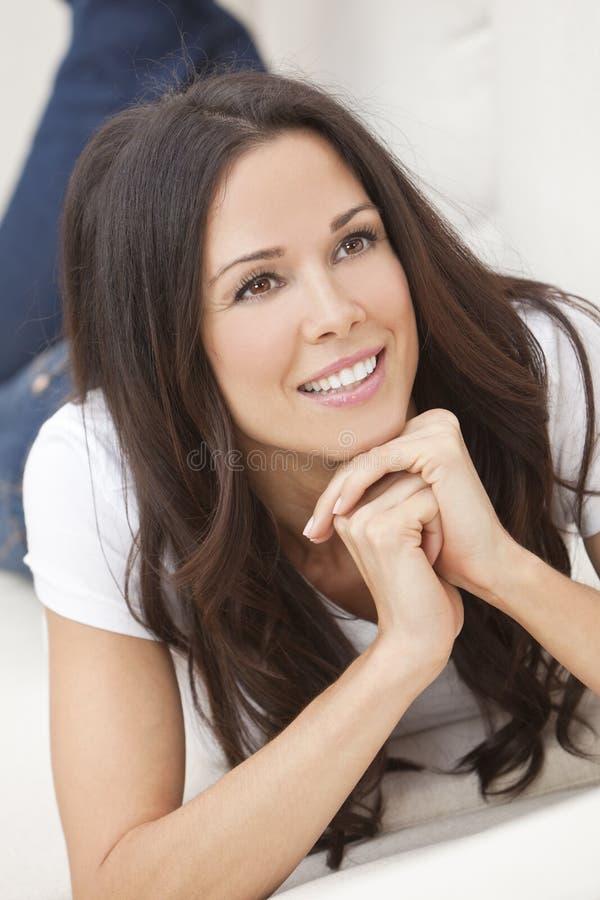 Mujer hermosa sonriente feliz que pone en el sofá fotos de archivo libres de regalías