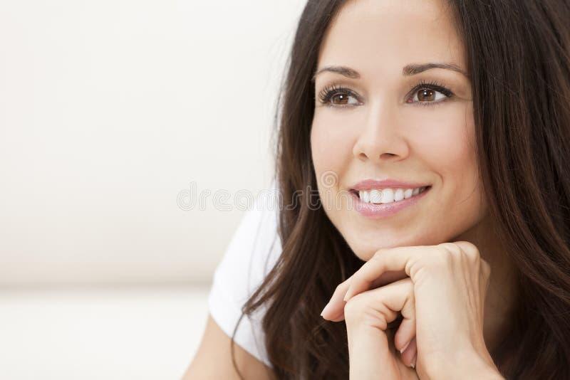Mujer hermosa sonriente feliz que se reclina sobre sus manos imagen de archivo libre de regalías