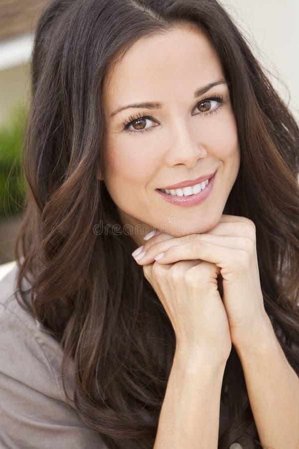 Mujer hermosa sonriente feliz que se reclina sobre sus manos