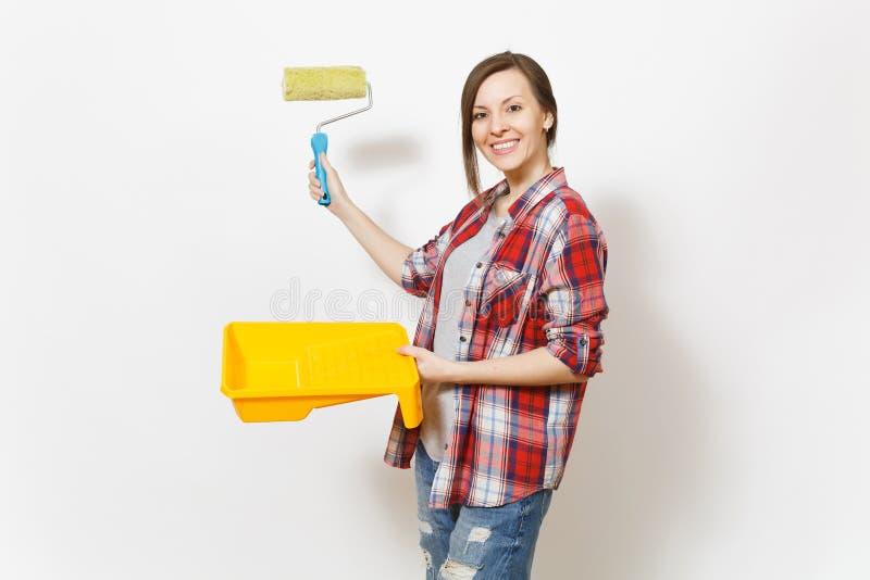 Mujer hermosa sonriente joven que sostiene la bandeja de la pintura, señalando el rodillo de pintura para la pintura de pared en  foto de archivo