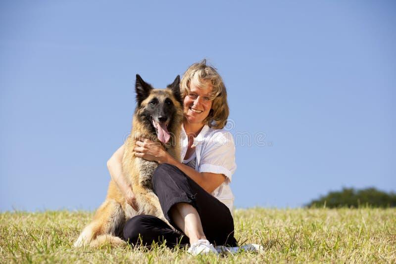 Mujer hermosa sonriente que abraza su perro imagenes de archivo