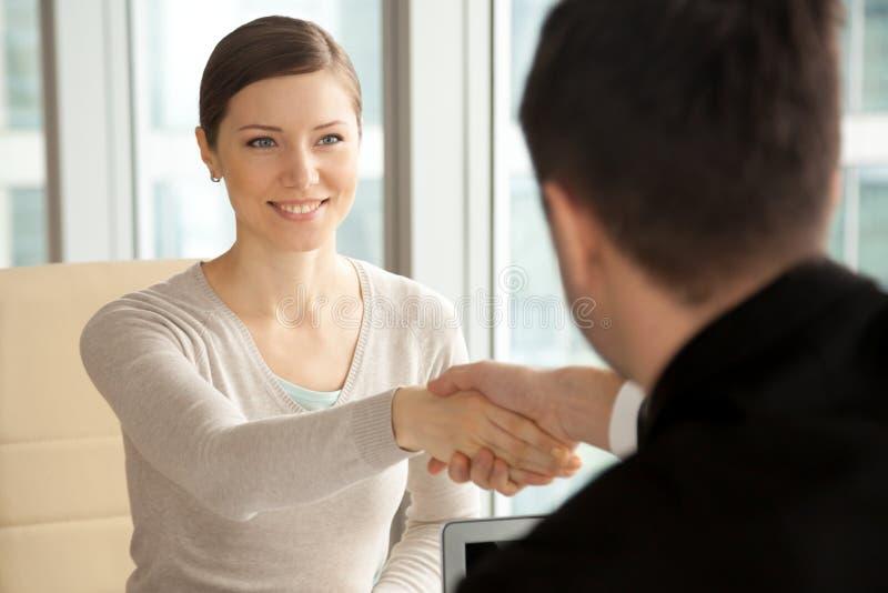 Mujer hermosa sonriente que sacude la mano masculina, llegando el trabajo inter imagenes de archivo