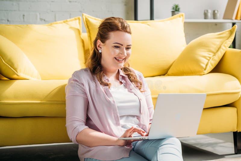 mujer hermosa sonriente que se sienta en piso y usar el ordenador portátil fotos de archivo libres de regalías