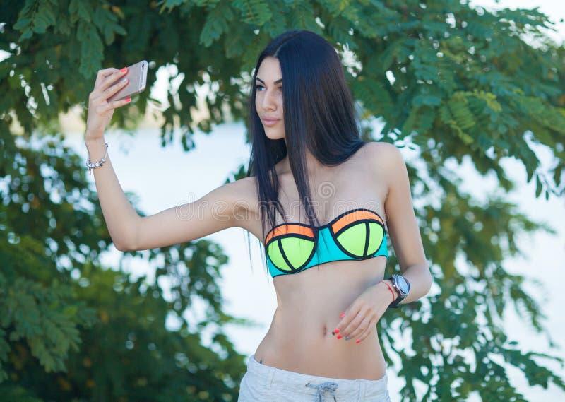 Mujer hermosa sonriente que toma el sol en una playa Foco en muchacha imagen de archivo libre de regalías