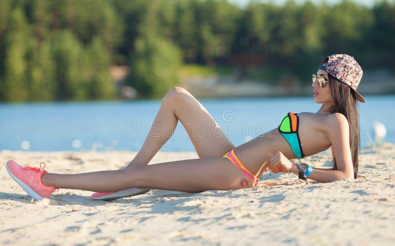 Mujer hermosa sonriente que toma el sol en una playa Foco en muchacha fotografía de archivo libre de regalías