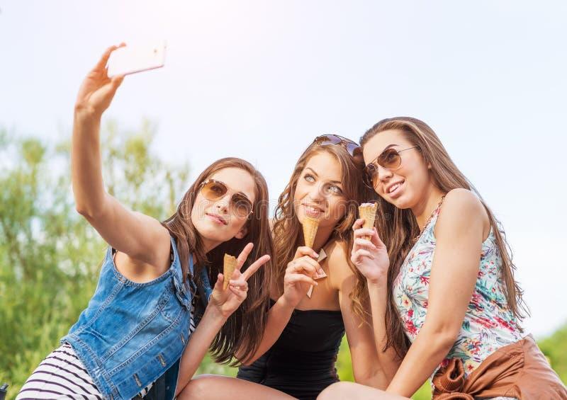 Mujer hermosa tres que come el helado durante el selfie que hace la foto fotos de archivo