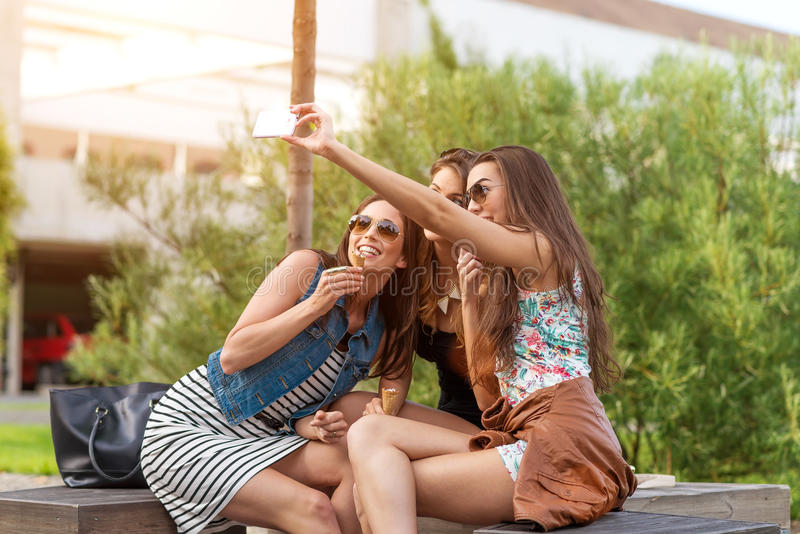 Mujer hermosa tres que come el helado durante el selfie que hace la foto imagenes de archivo
