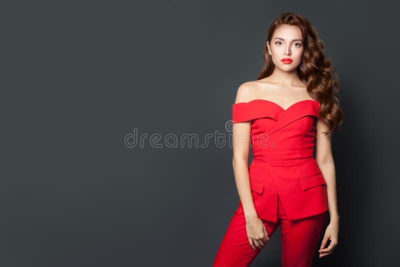 Mujer hermosa vestida con traje rojo con fondo gris Magnífico modelo con peinado perfecto fotografía de archivo