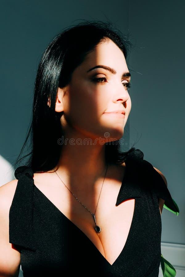 Mujer hermosa vestida en la sentada negra en el piso fotografía de archivo libre de regalías