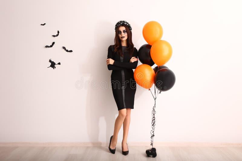 Mujer hermosa vestida para Halloween cerca de la pared adornada ligera fotos de archivo libres de regalías