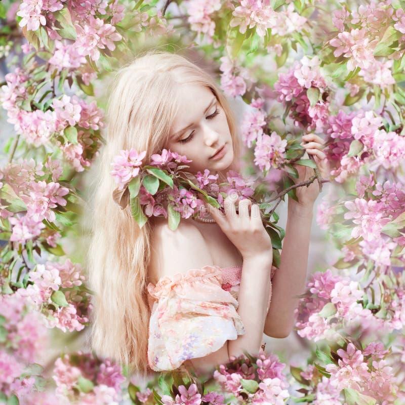 Mujer hermosa y árbol floreciente Chica joven de la belleza en jardín fotos de archivo libres de regalías
