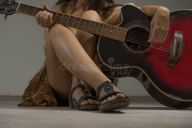 Mujer hermosa y atractiva con la guitarra acústica imagen de archivo libre de regalías