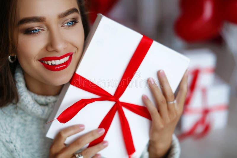 Mujer hermosa y atractiva atractiva con sonrisa perfecta y los dientes Con maquillaje en el cumplea?os o el regalo de la tenencia foto de archivo libre de regalías