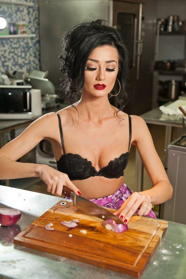 Mujer hermosa y atractiva en la cocina Morenita sonriente que prepara la comida Chica joven que lleva el sujetador negro que cort imágenes de archivo libres de regalías