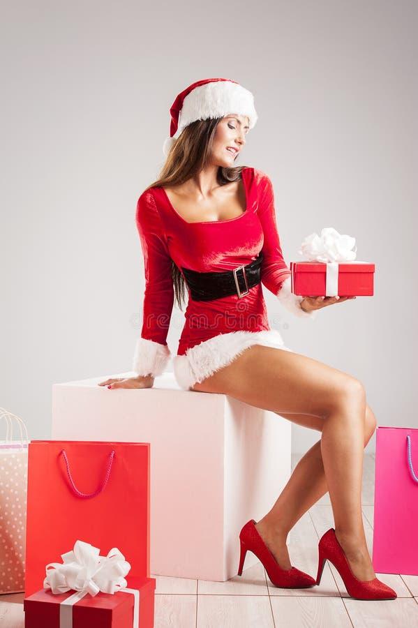 Mujer hermosa y atractiva que lleva el traje de Papá Noel y que sostiene un regalo fotos de archivo