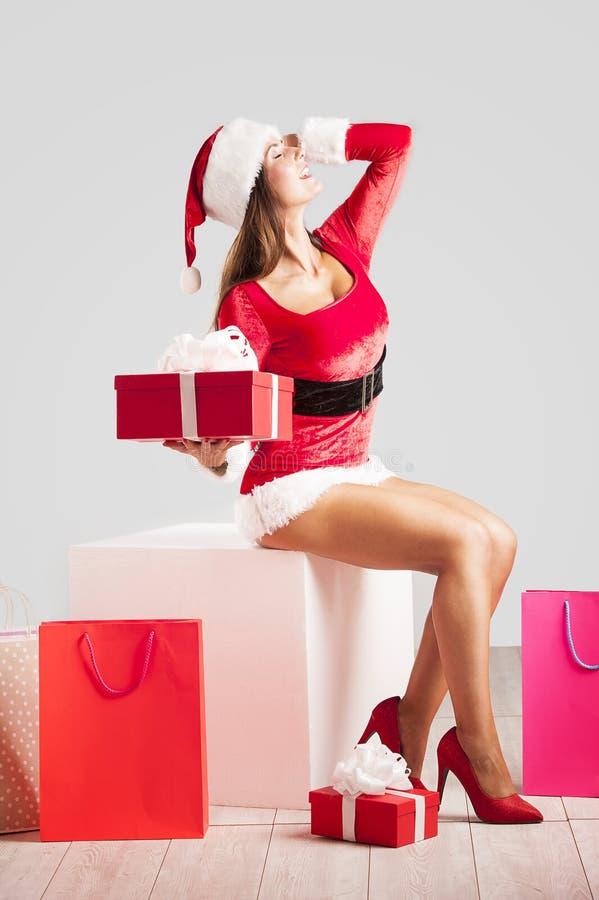 Mujer hermosa y atractiva que lleva el traje de Papá Noel y que sostiene un regalo imagenes de archivo