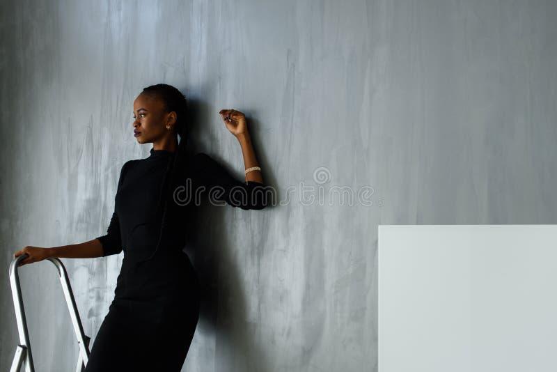 Mujer hermosa y de negro sexy en el vestido oscuro que presenta mirando la mano lejos que se inclina en la pared gris el estudio fotos de archivo