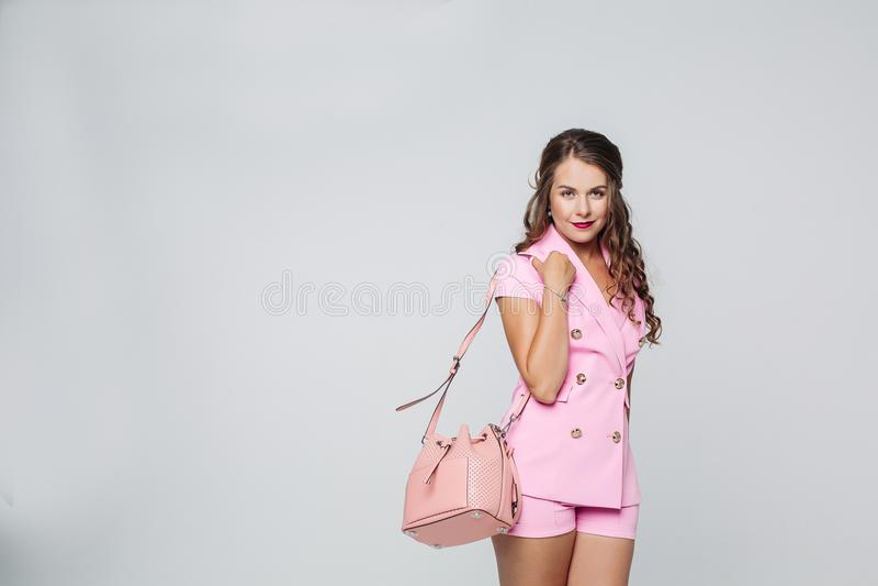 Mujer hermosa y elegante que lleva en el traje rosado que presenta en el estudio fotos de archivo