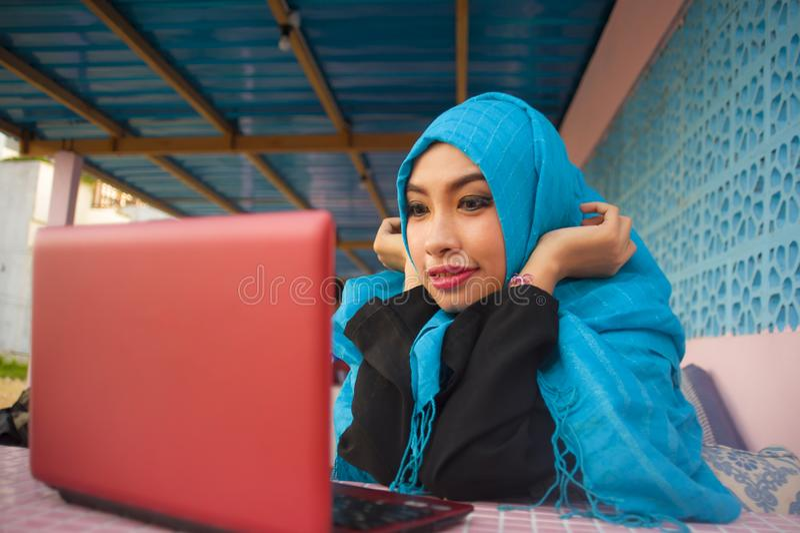 Mujer hermosa y feliz en la bufanda musulmán de la cabeza del hijab que trabaja con el ordenador portátil o que tiene establecimi imágenes de archivo libres de regalías