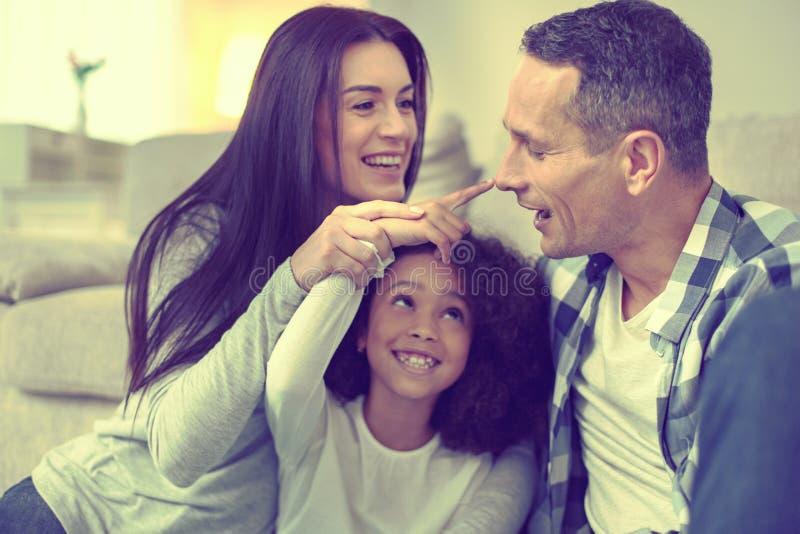 Mujer hermosa y hombre hermoso que toman buen cuidado de su hija adoptada foto de archivo libre de regalías