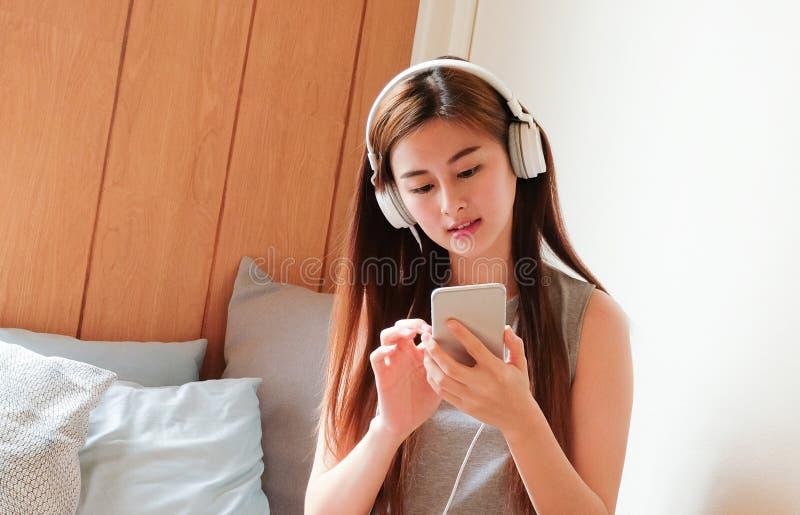 Mujer hermosa y linda asiática con el teléfono móvil y el auricular l fotografía de archivo libre de regalías