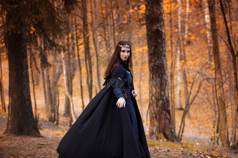 Mujer hermosa y misteriosa joven en bosque, en capa negra con la capilla, la imagen del duende del bosque o la bruja fotos de archivo libres de regalías