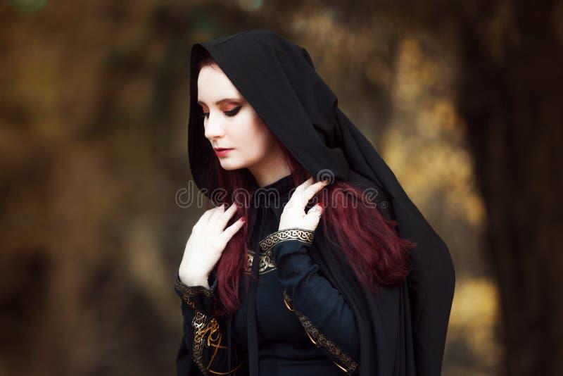 Mujer hermosa y misteriosa joven en bosque, en capa negra con la capilla, la imagen del duende del bosque o la bruja foto de archivo libre de regalías
