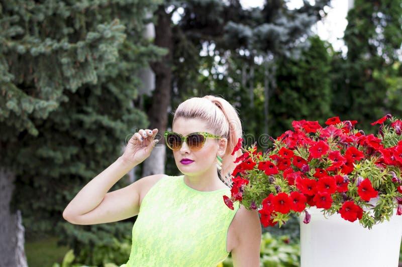 Mujer hermosa y petunia hermosa imagen de archivo