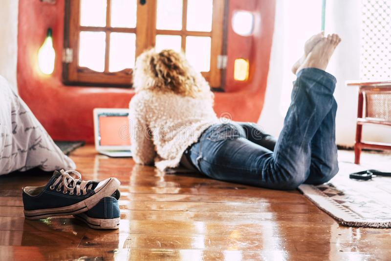 Mujer hipster se sienta en el suelo en casa trabajando o haciendo compras modernas con ordenador portátil conectado a Internet -  fotografía de archivo