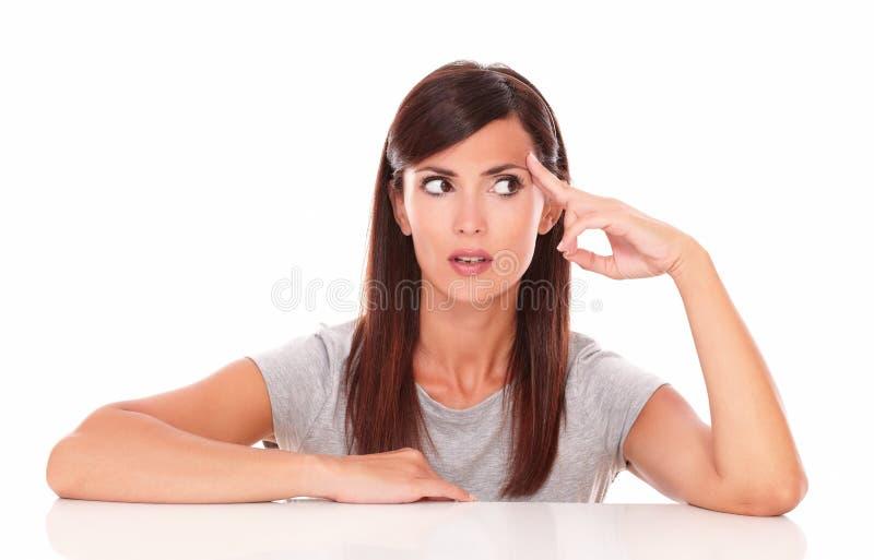 Mujer hispánica adulta que se pregunta mientras que mira a la izquierda fotos de archivo