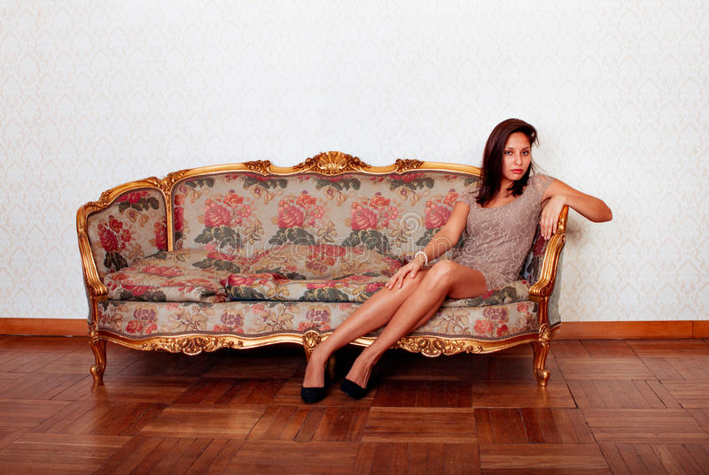 Mujer hispánica atractiva que acuesta en el sofá imagen de archivo libre de regalías