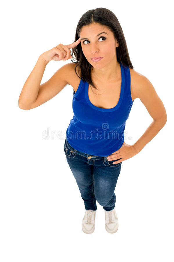 Mujer hispánica en top y vaqueros que señalan a su cabeza que piensa y que se pregunta confundida fotografía de archivo
