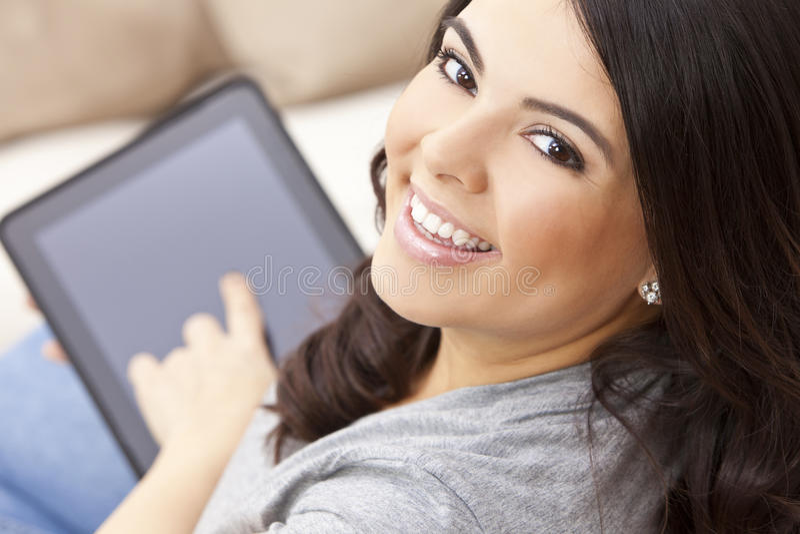 Mujer hispánica feliz que usa el ordenador o el iPad de la tablilla imagenes de archivo