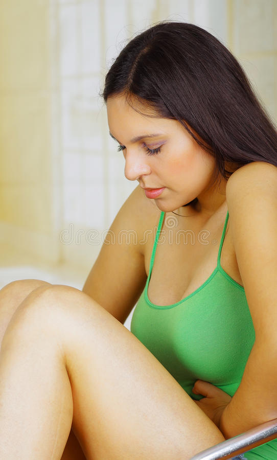 Mujer hispánica hermosa joven que usa una blusa verde en la expresión dolorosa que toca su vientre y que dobla sus piernas foto de archivo libre de regalías